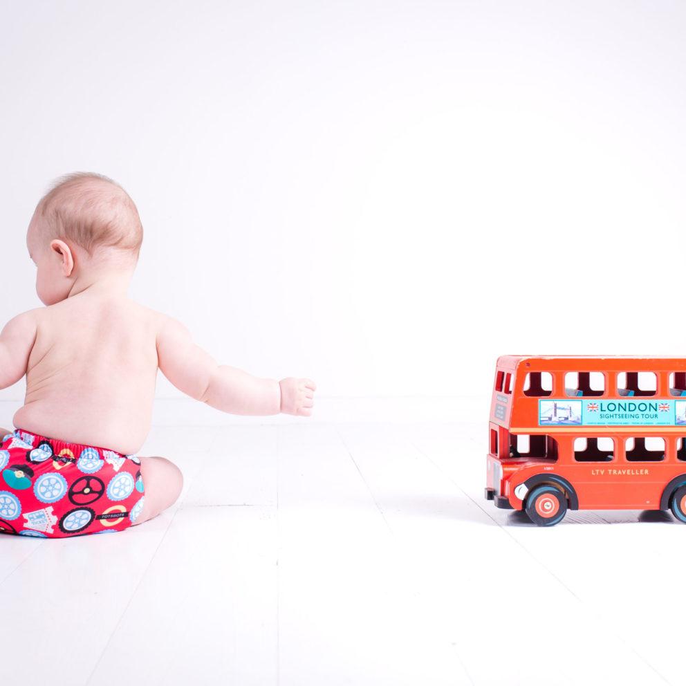 Un petit garçon joue dans sa couche lavable tout-en-deux Totsbots Peenut un bus à deux étages miniature